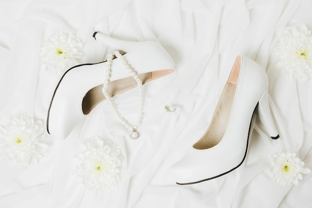 An overhead view of chrysanthemum; necklace; earrings and wedding high heels on white scarf Free Photo
