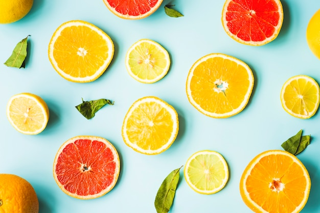 Overhead view of citrus fruit slices on blue background Free Photo