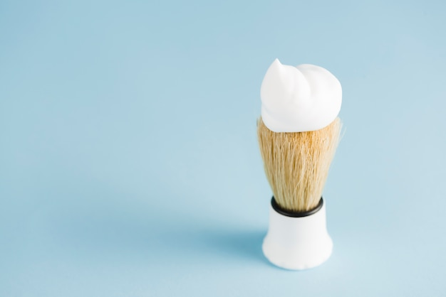 An overhead view of classic shaving brush with white foam against blue background Free Photo