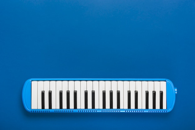 An overhead view of classical piano black and white keyboard on blue background Free Photo