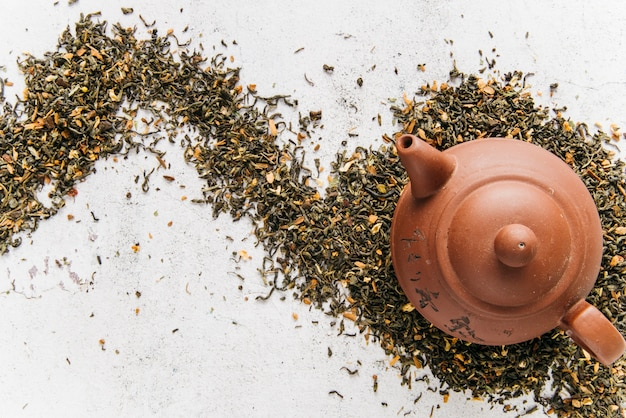 An overhead view of clay teapot on dry tea herbs over the concrete backdrop Free Photo