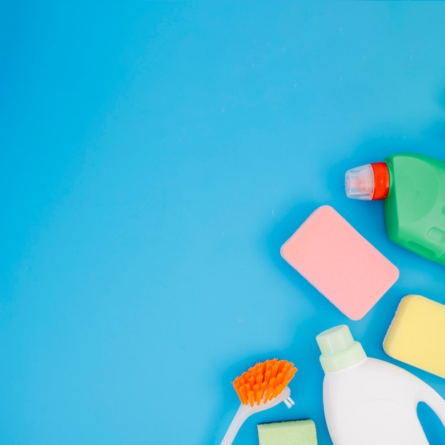 An overhead view of cleaning products on blue background Free Photo