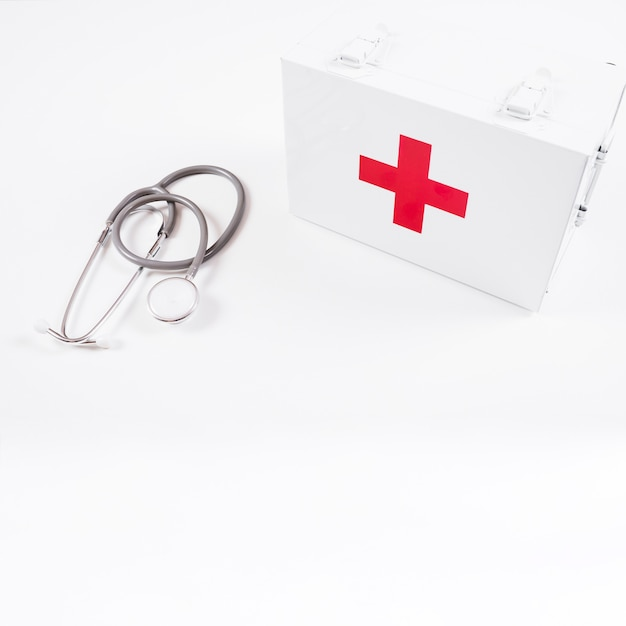 Overhead view of closed first aid kit and stethoscope on white background Free Photo