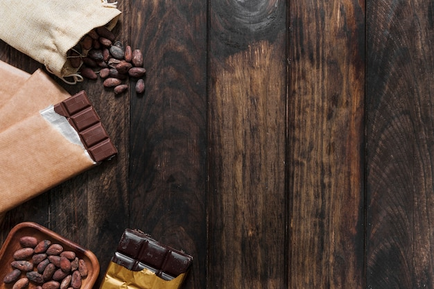 Overhead view of cocoa beans and chocolate bars on wooden table Free Photo