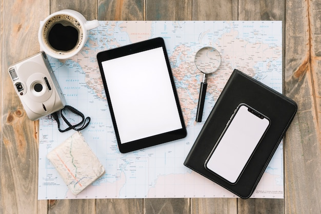 An overhead view of coffee cup; camera; digital tablet; cell phone; magnifying glass and diary on map against wooden table Free Photo