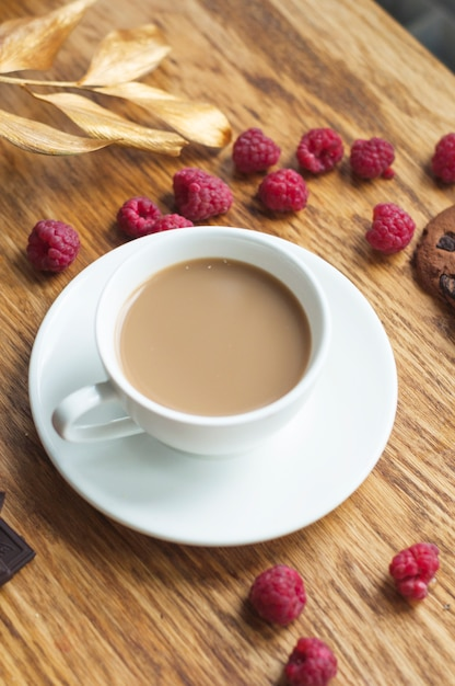 An overhead view of coffee cup on saucer with fresh raspberries on wooden table Free Photo