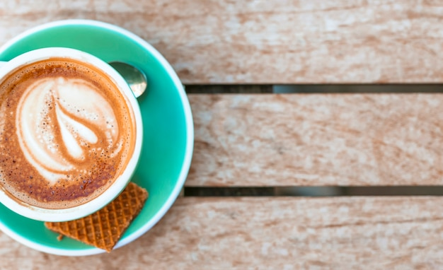 An overhead view of coffee cup with heart latte art on wooden table Free Photo