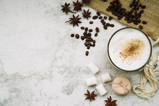 Overhead view of coffee cup with star anise; coffee beans; marshmallow and macaroon Free Photo