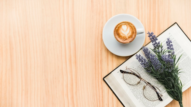 Overhead view of coffee latte,lavender flower,spectacles and notebook on wooden background Free Photo