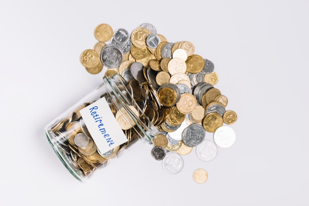 Overhead view of coins spilled out from retirement glass container on white background Free Photo