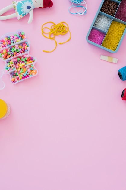 An overhead view of colorful beads in case on pink background Free Photo