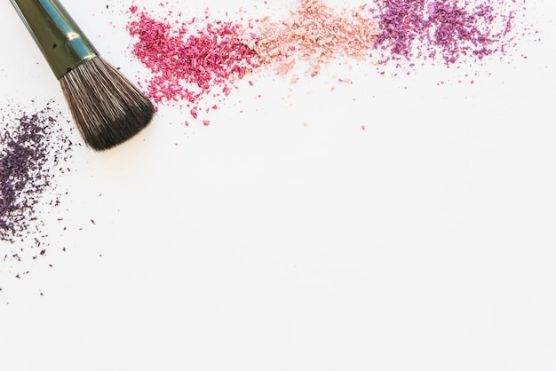 An overhead view of colorful cosmetic face powder and make-up brush on white backdrop Free Photo