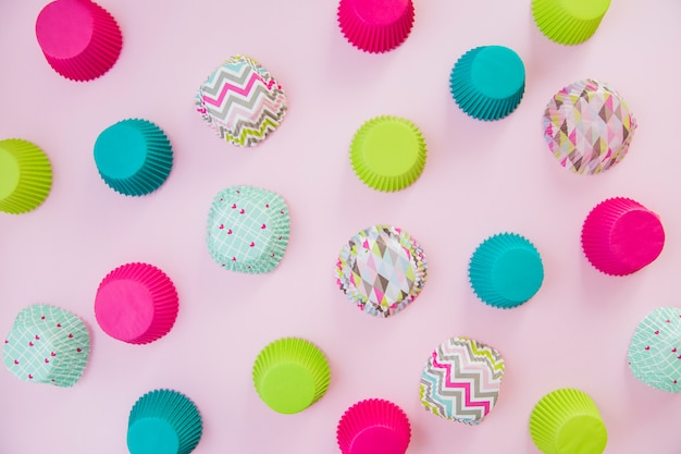 An overhead view of colorful cupcake paper cups on pink backdrop Free Photo