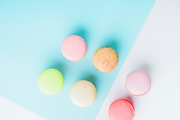 An overhead view of colorful macaroons on blue and white dual background Free Photo