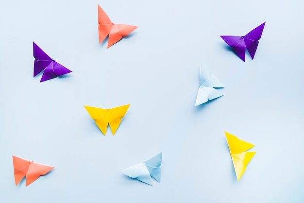 An overhead view of colorful origami paper butterflies on blue background Premium Photo