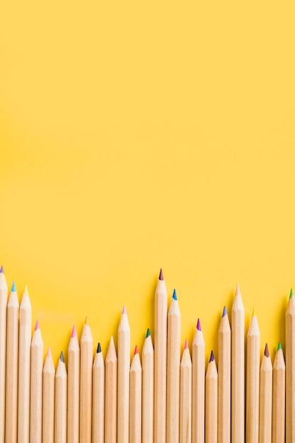 Overhead view of colorful pencils on yellow backdrop Premium Photo