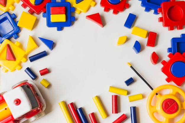 Overhead view of colorful plastic blocks on white background Free Photo