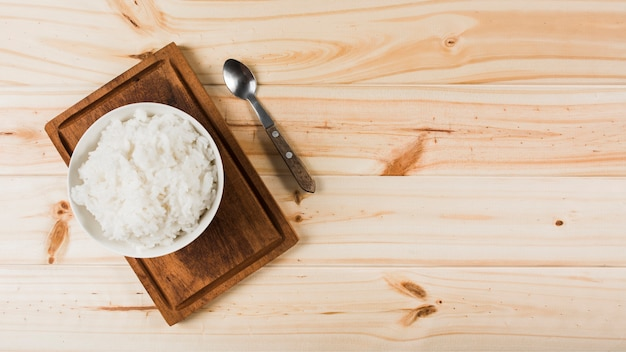 An overhead view of cooked white rice bowl on wooden tray with spoon Free Photo