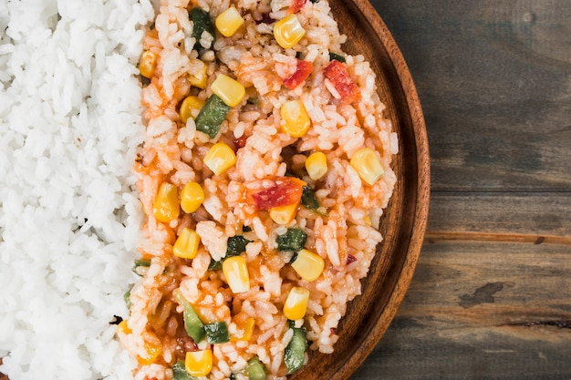 An overhead view of cooked white rice and chinese fried rice with vegetables on wooden tray Free Photo