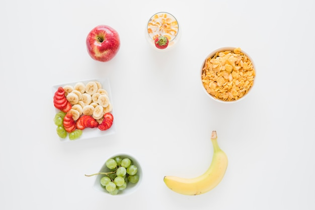 An overhead view of cornflakes with apple; banana; strawberry and grapes isolated on white backdrop Free Photo