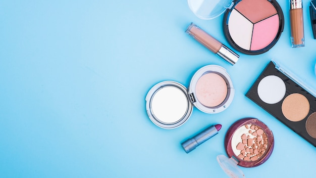 An overhead view of cosmetic face powder; lipstick; and foundation on blue backdrop Free Photo
