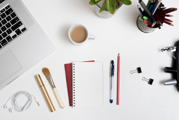 Overhead view of cosmetic products; office stationery; laptop and coffee cup with plant on office desk Free Photo