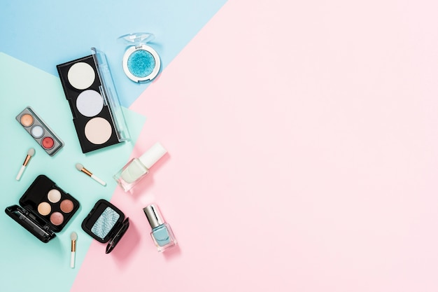 An overhead view of cosmetic products over the pastel background Free Photo