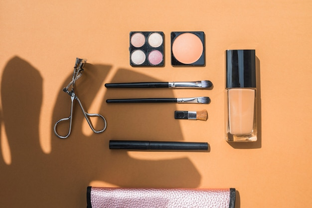 Overhead view of cosmetic products with brushes on orange backdrop Free Photo