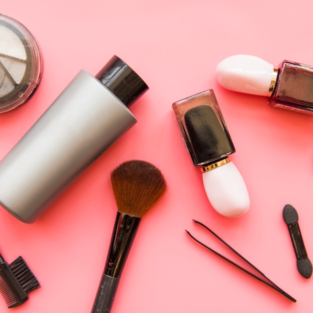 An overhead view of cosmetics makeup products on pink backdrop Free Photo