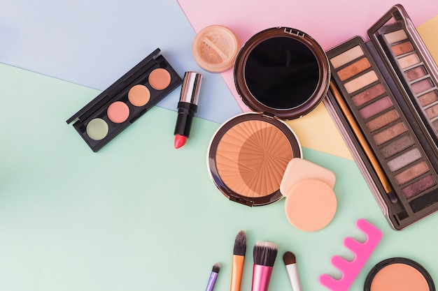 An overhead view of cosmetics products on colored background Free Photo