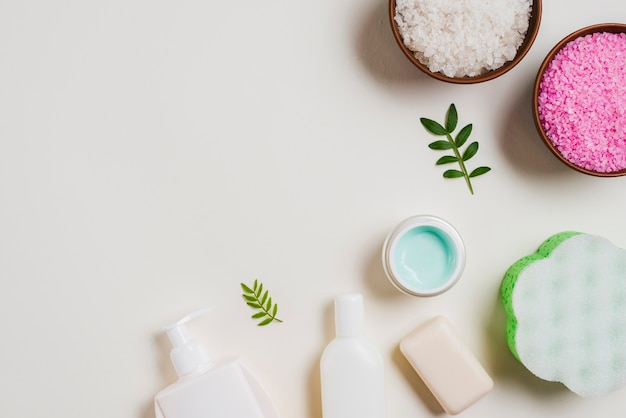 An overhead view of cosmetics products with salt bowls on white backdrop Free Photo