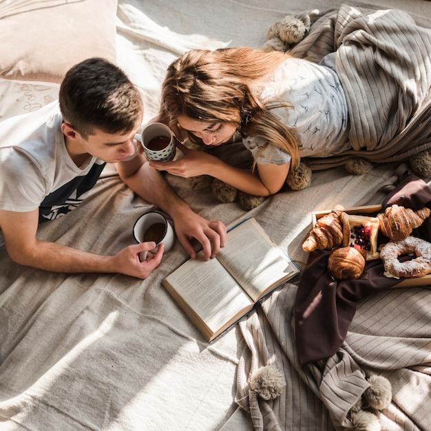 An overhead view of couple lying on bed holding cup of coffee reading book Free Photo