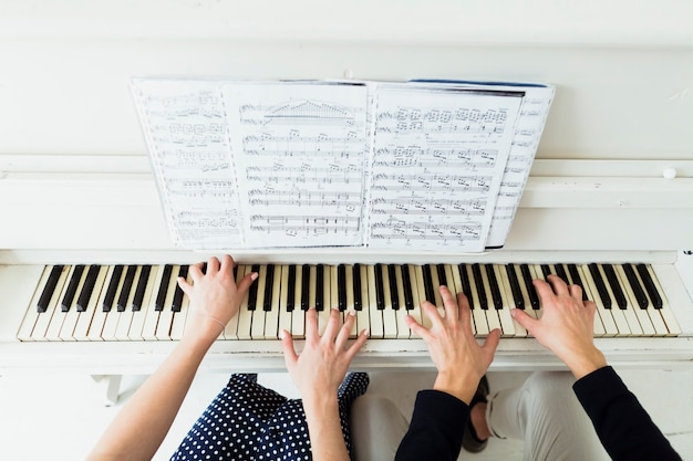 An overhead view of couple's hand playing piano with musical sheet Free Photo
