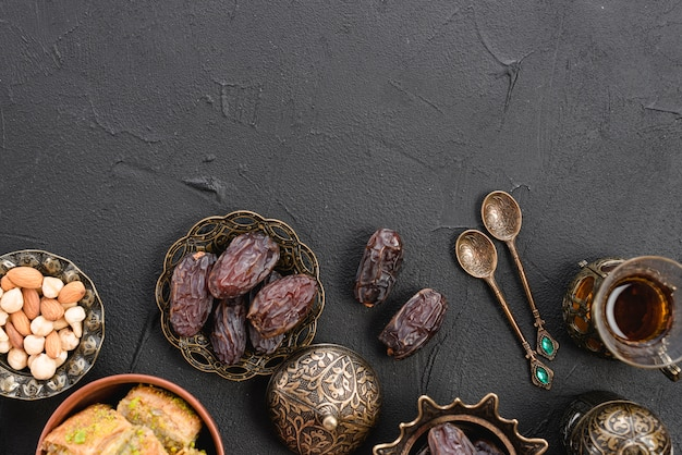 An overhead view of dates in the traditional turkish metallic bowl; spoons and tea glasses on black backdrop Free Photo