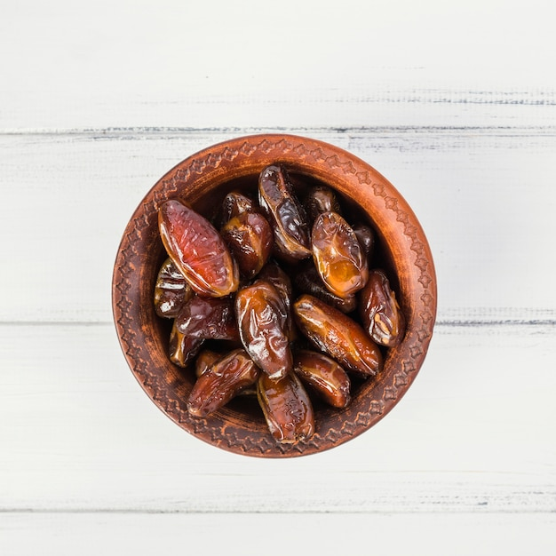 An overhead view of dates in a wooden bowl on white wooden table Free Photo