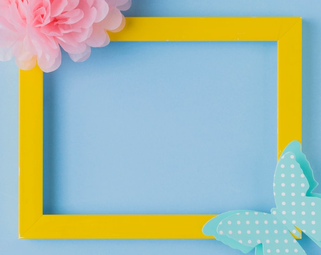 Overhead view of decorative yellow photo frame with flower and butterfly cutout Free Photo