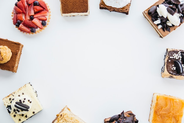 Overhead view of delicious pastries forming frame on white backdrop Free Photo