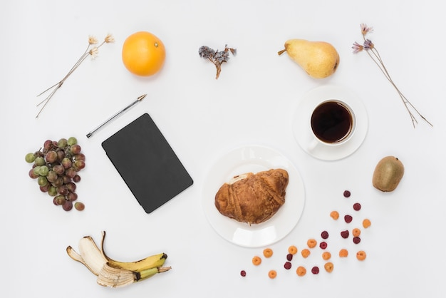 An overhead view of diary and pen with fruits; coffee and croissant isolated on white background Free Photo