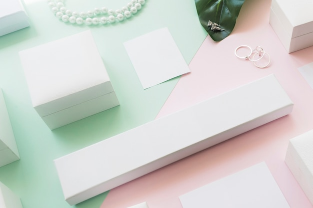 Overhead view of different white boxes on two green and pink paper backdrop Free Photo