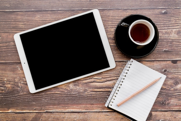 An overhead view of digital tablet; coffee cup and spiral notebook with pencil on wooden textured table Free Photo