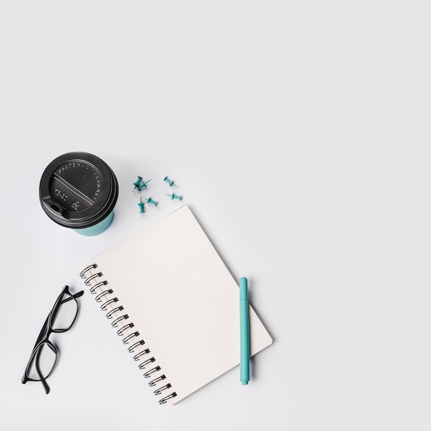 An overhead view of disposable coffee cup; push pins; pen; eyeglasses and spiral notepad on white background Free Photo