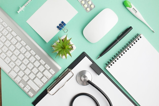 Overhead view of doctor's desk with pills and office supplies Free Photo