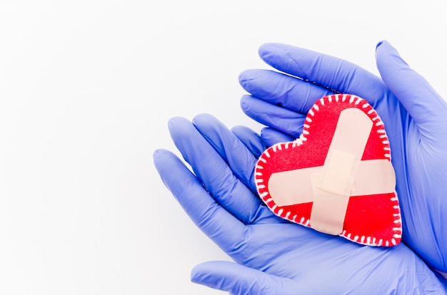 An overhead view of doctor's hand with surgical gloves holding red heart with bandages isolated on white backdrop Free Photo