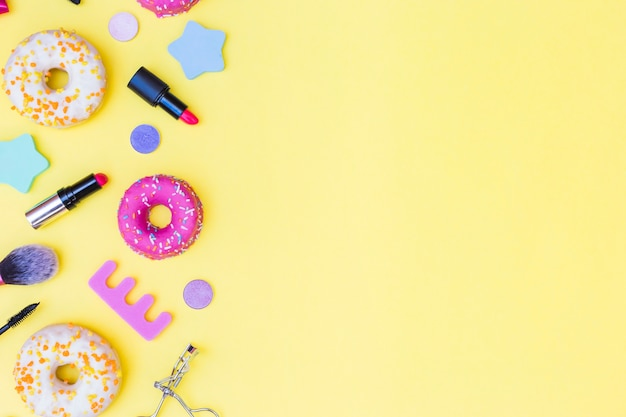 An overhead view of donuts; lipstick; eyelash curler; makeup brush and toe divider on yellow background Free Photo
