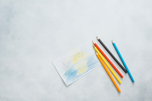 Overhead view of drawn paper and color pencils on white background Free Photo
