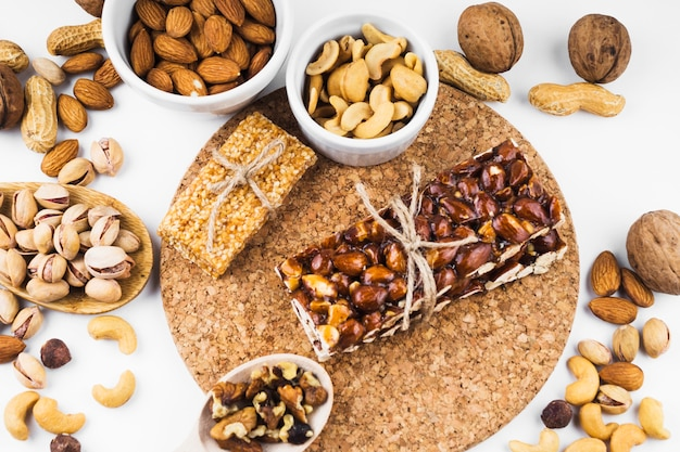 An overhead view of dried fruits and energy bar on white backdrop Free Photo