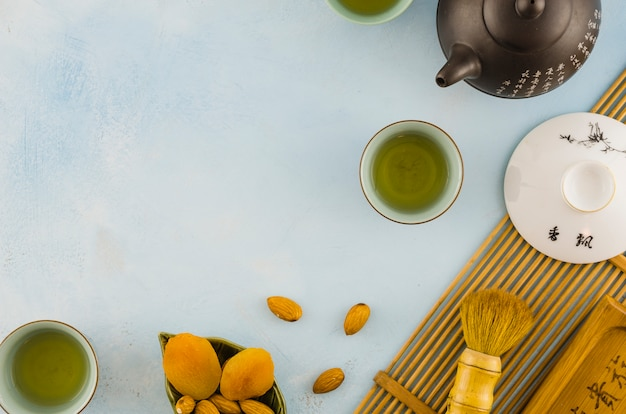 An overhead view of dried fruits; tea cups and teapot on textured backdrop Free Photo