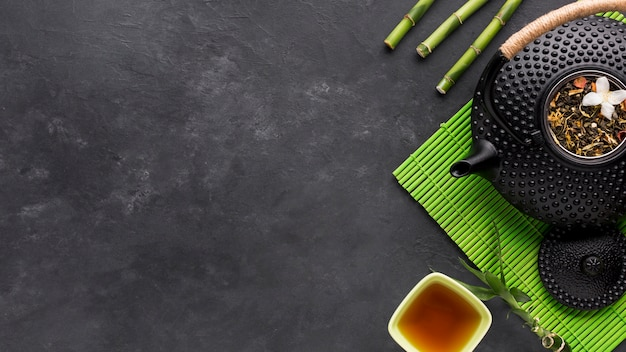 Overhead view of dried herb and bamboo stick with teapot on black backdrop Free Photo