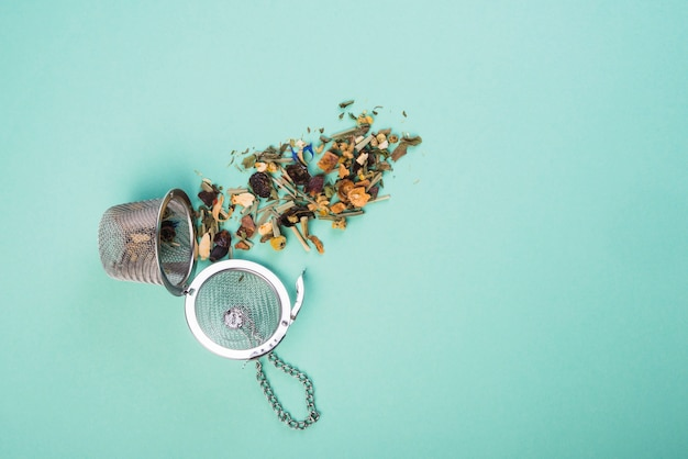 An overhead view of dried herbal tea with strainers on blue background Free Photo