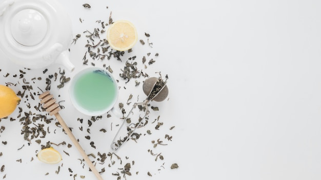 An overhead view of dry tea leaves; tea strainer; lemon; green tea; honey dipper and teapot on white backdrop Free Photo